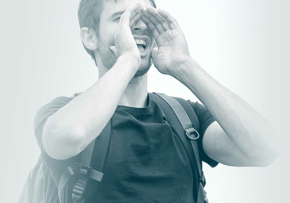 Photo of a man wearing a backpack, yelling out with his hands cupped around his mouth. Showing how our employee benefits company helps you to communicate.